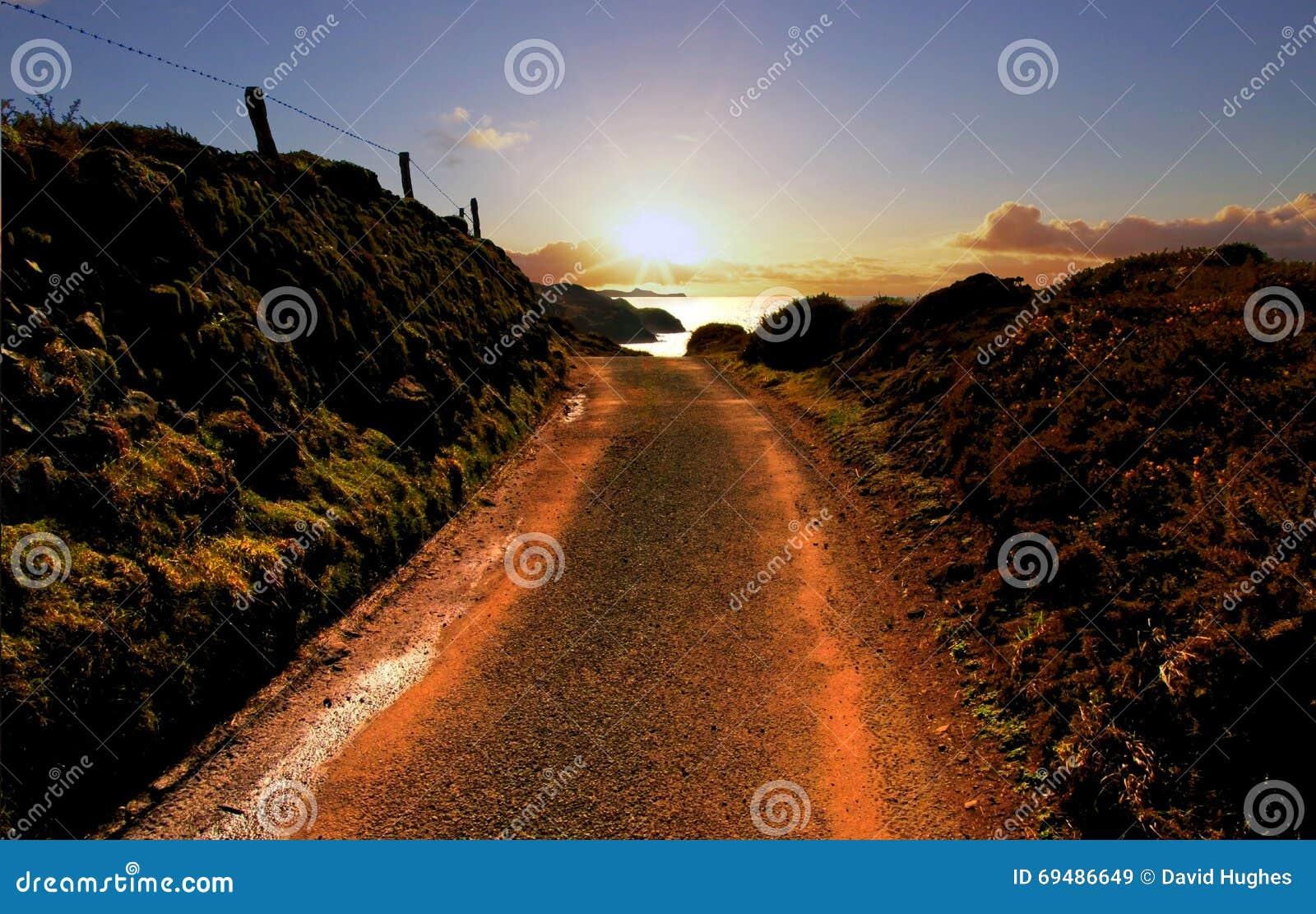 Strada che conduce al tramonto sopra Pembroke Coast