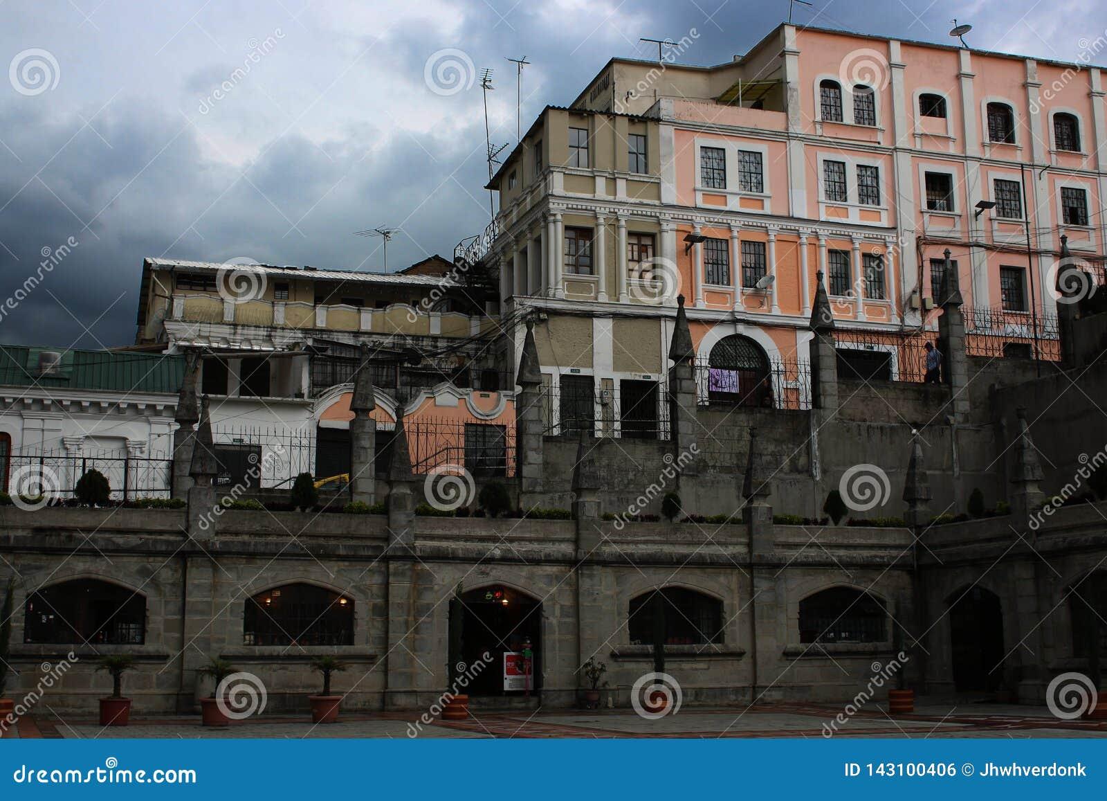 Strada grigio scuro e sporca con le costruzioni variopinte sui precedenti e su un cielo scuro in pieno delle nuvole a Quito Ecuad