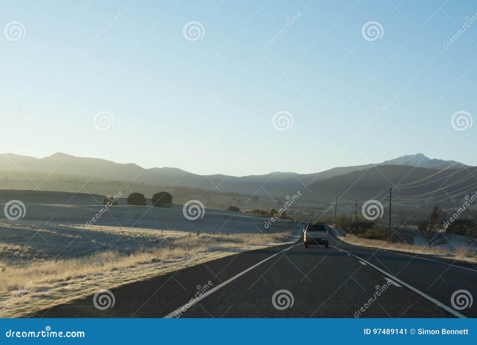 Strada principale del paese con le automobili che conducono verso le montagne all alba