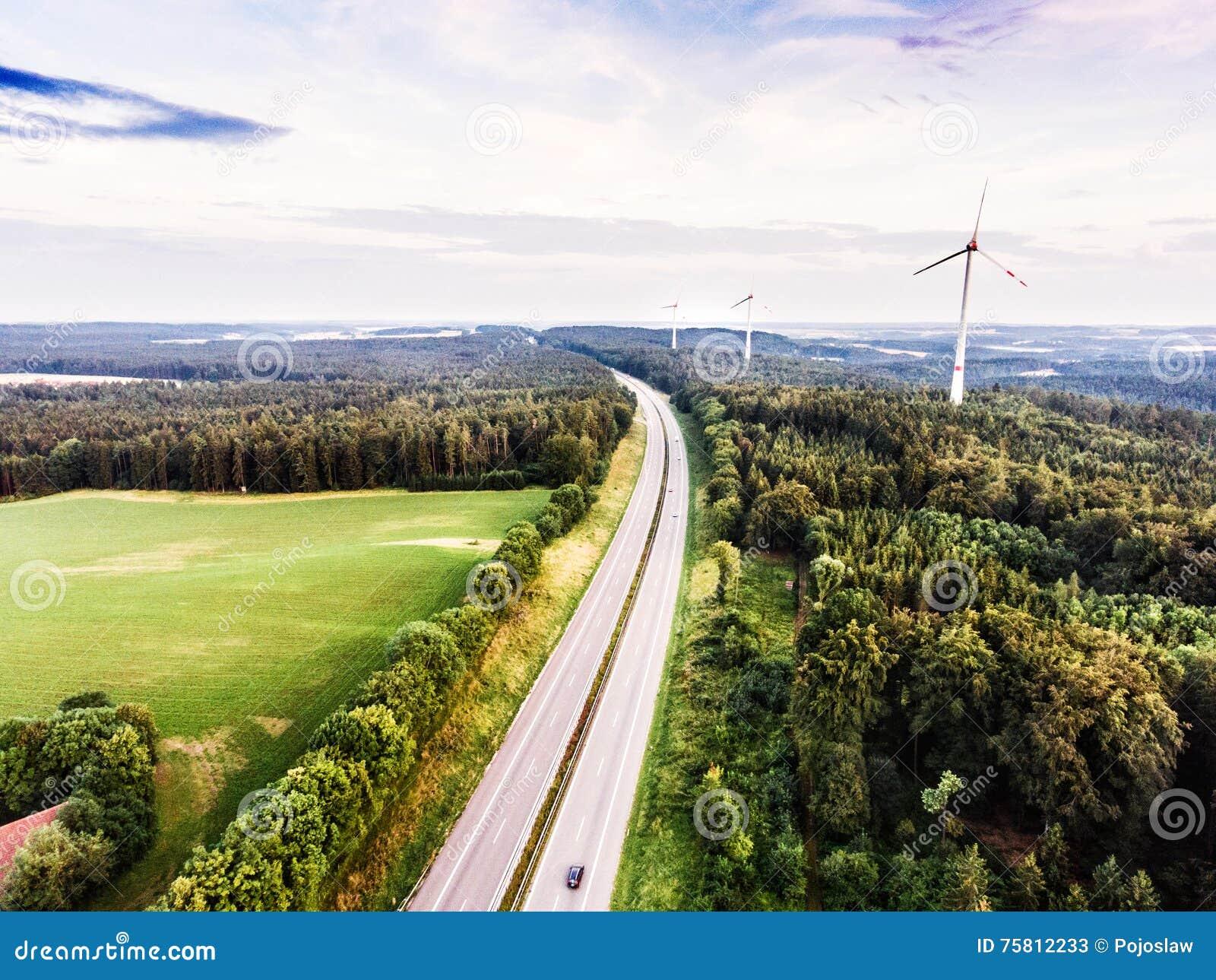 Strada principale in foresta verde, mulini a vento, cielo nuvoloso netherlands