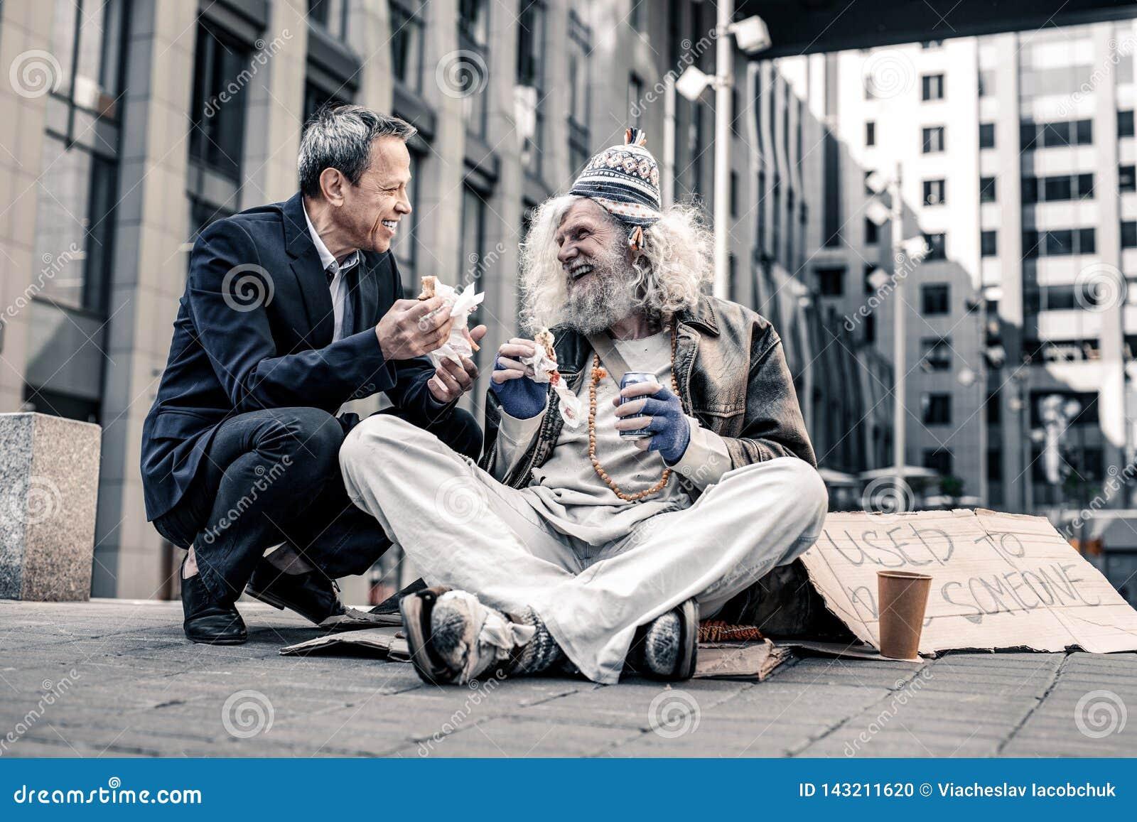 Strahlender schöner Mann, der angenehmes Gespräch mit schmutzigem Obdachlosem hat