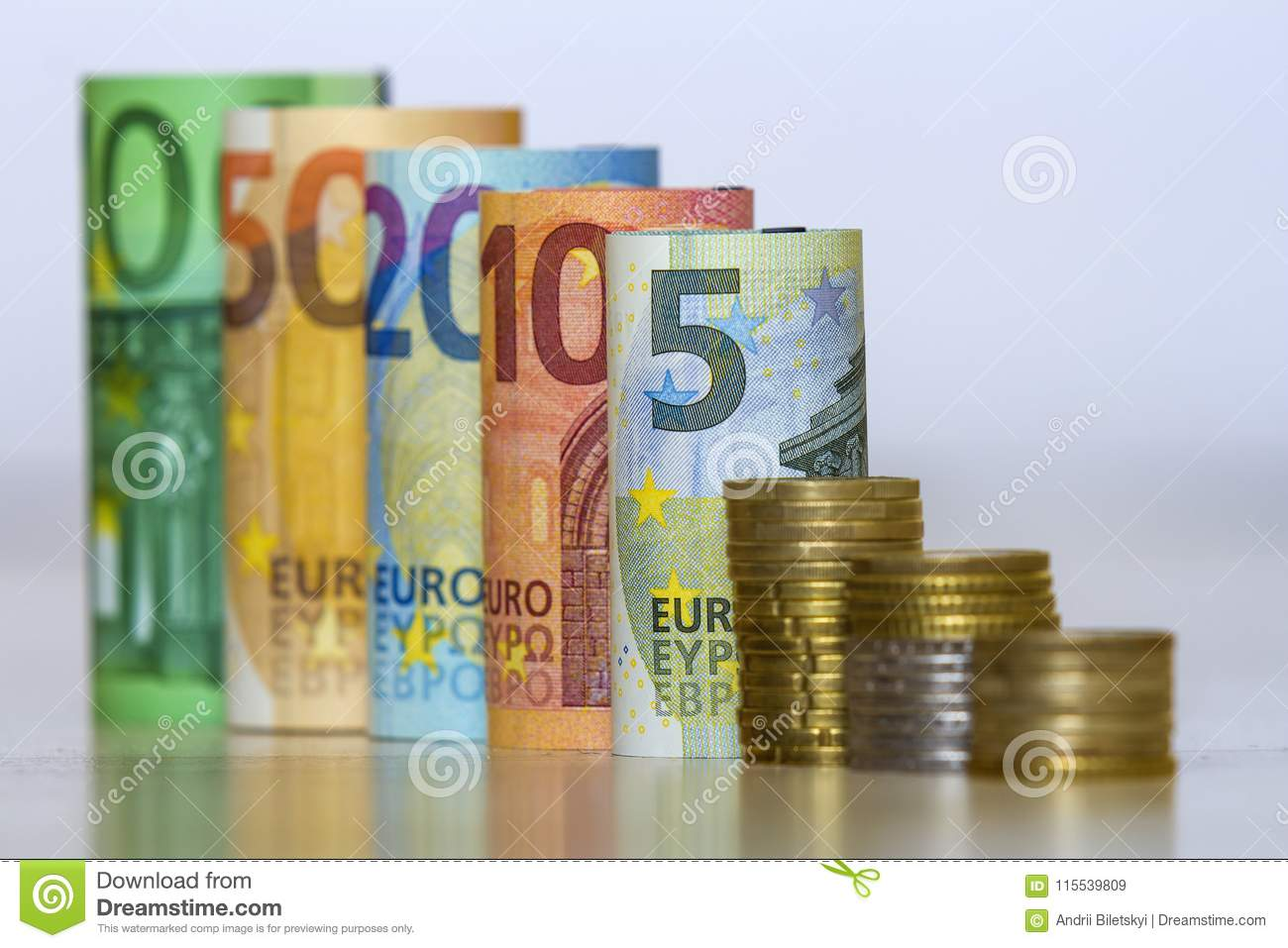 Straight row of accurately rolled hundred, fifty, twenty, ten and five new paper euro banknotes and pile of metallic coins isolate