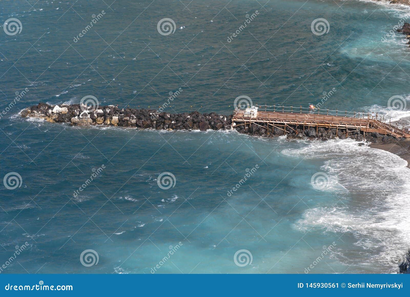 Strand, eind van het zwemmen seizoen in Sorrento Concrete die blokken als overzeese defensie in Italië worden gebruikt