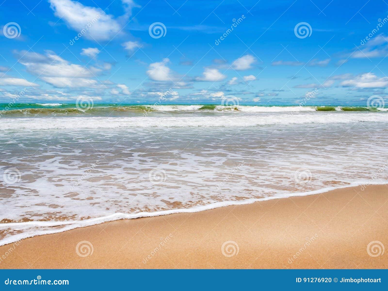 Strand med blå havs- och vitsand i blå himmel