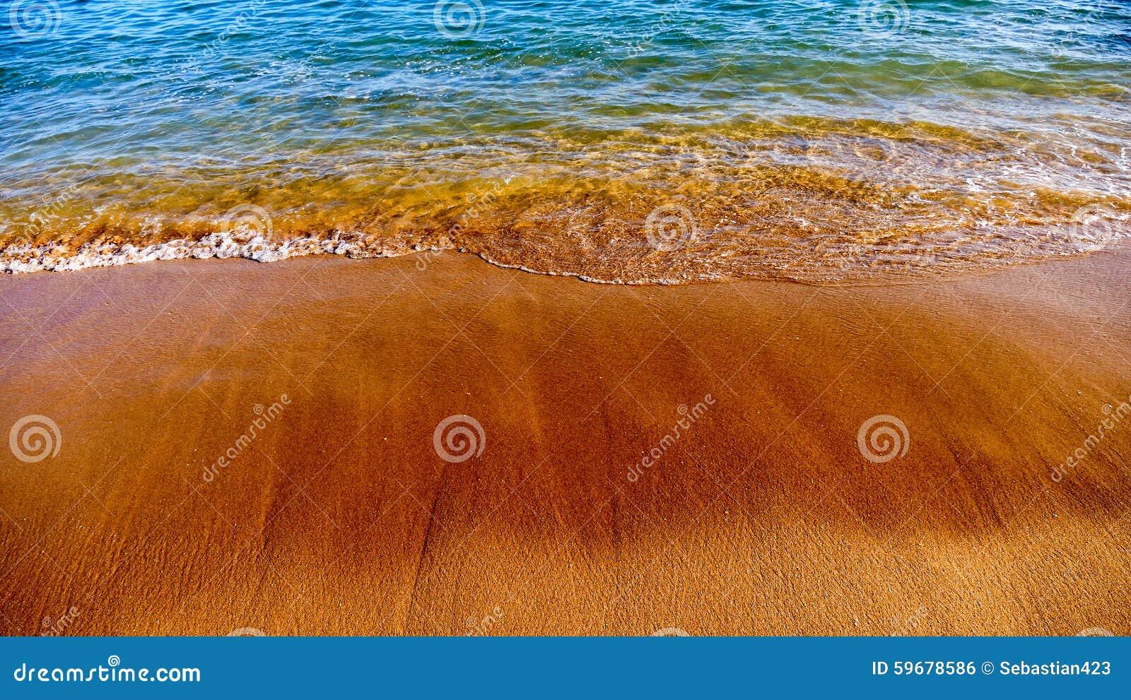 Strand met donker zand en blauw water