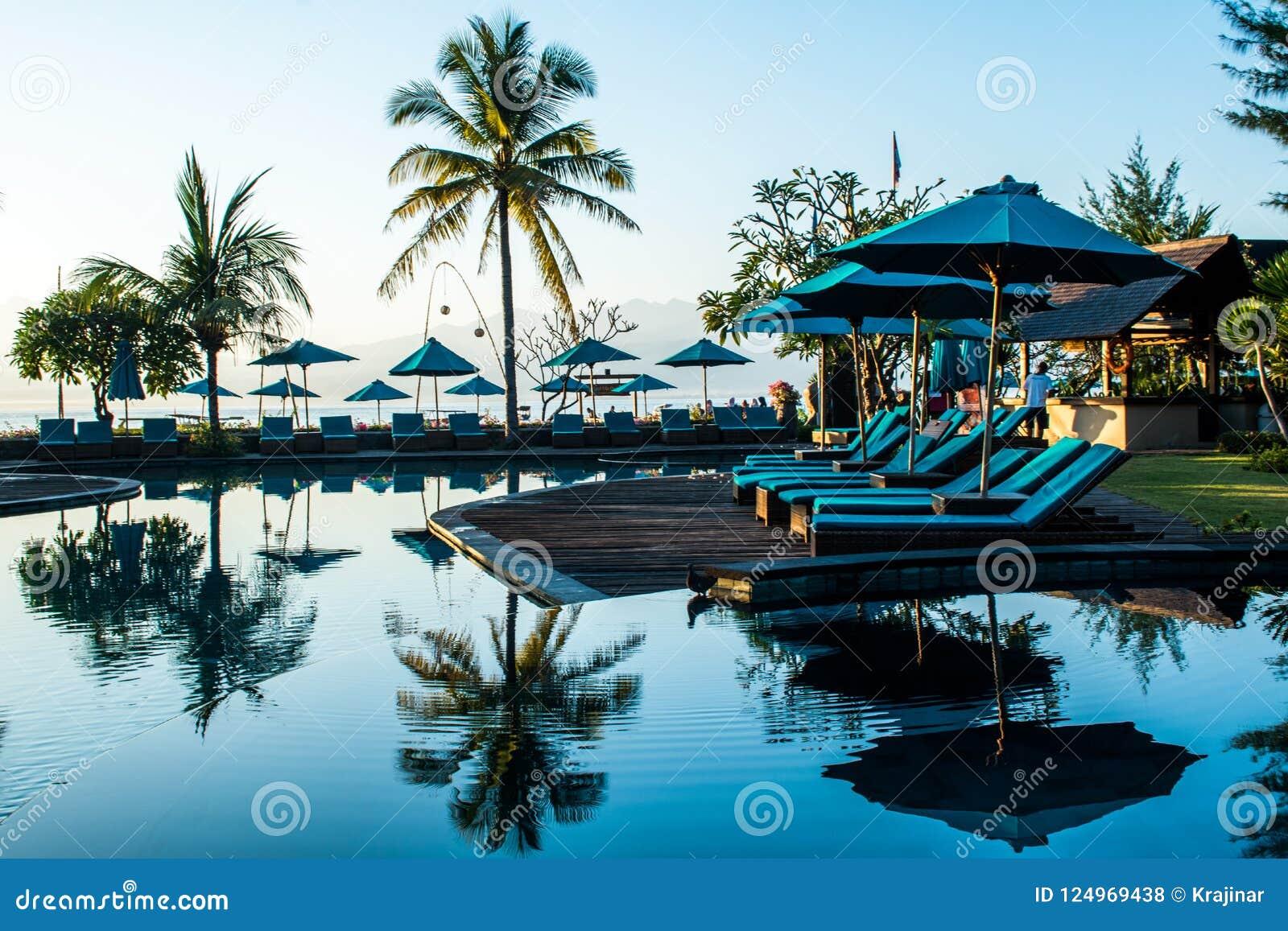 Strand sunbeds dichtbij zwembad in tropische toevlucht met palmen tijdens zonsondergang, Gili Trawangan, Lombok, Indonesië