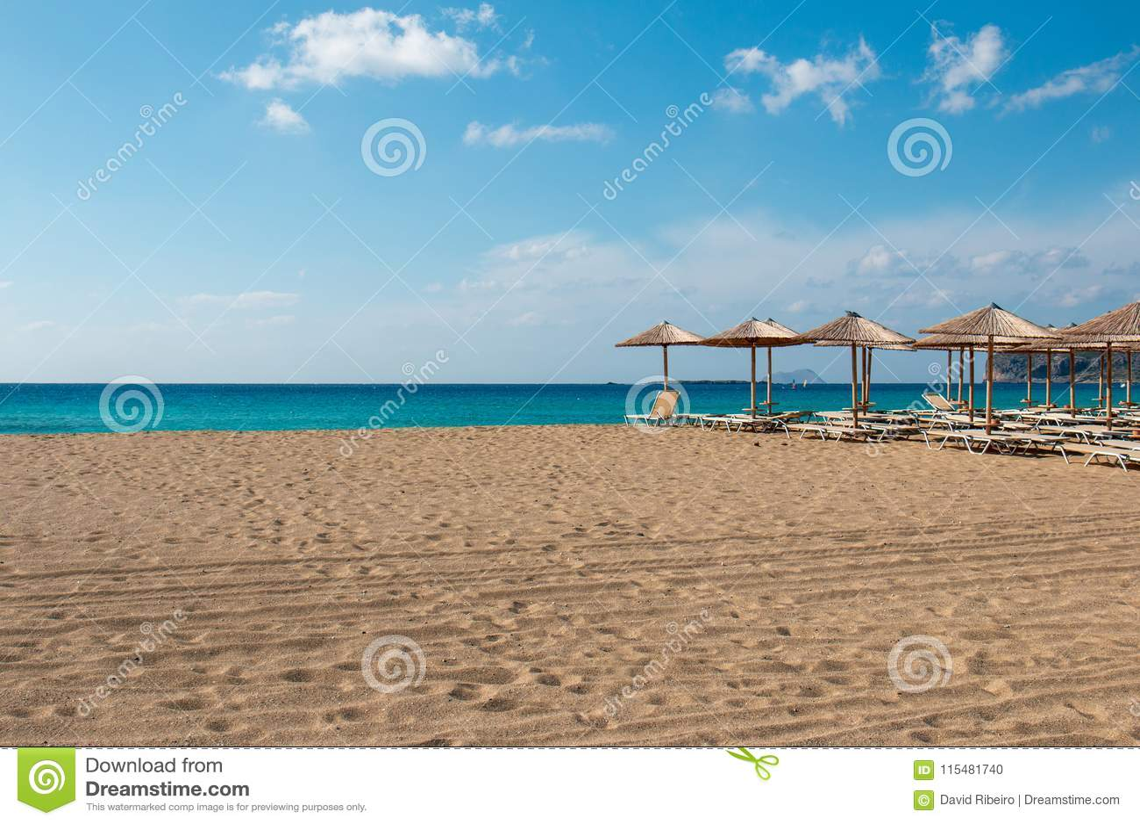 Strand sunbeds en parasols overziend turkoois water in Griekenland