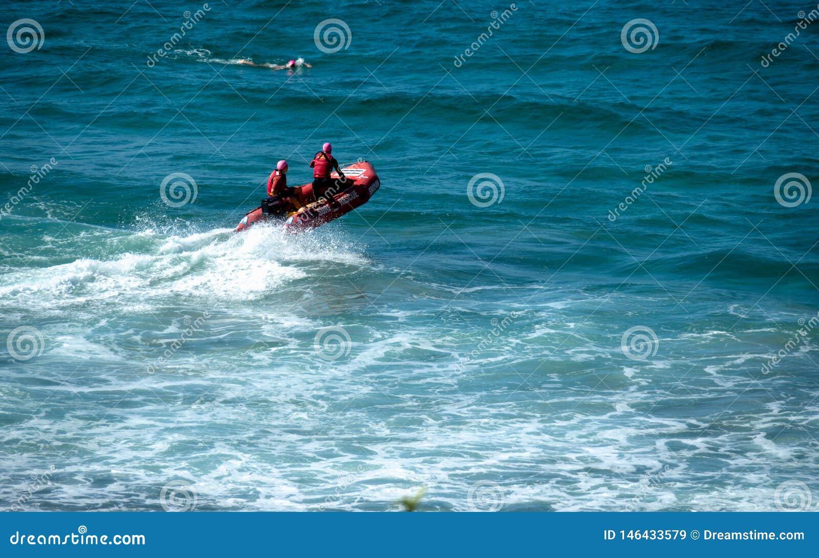 Strandbereden politie op een rode reddingsboot een surfer die dichtbij zwemmen