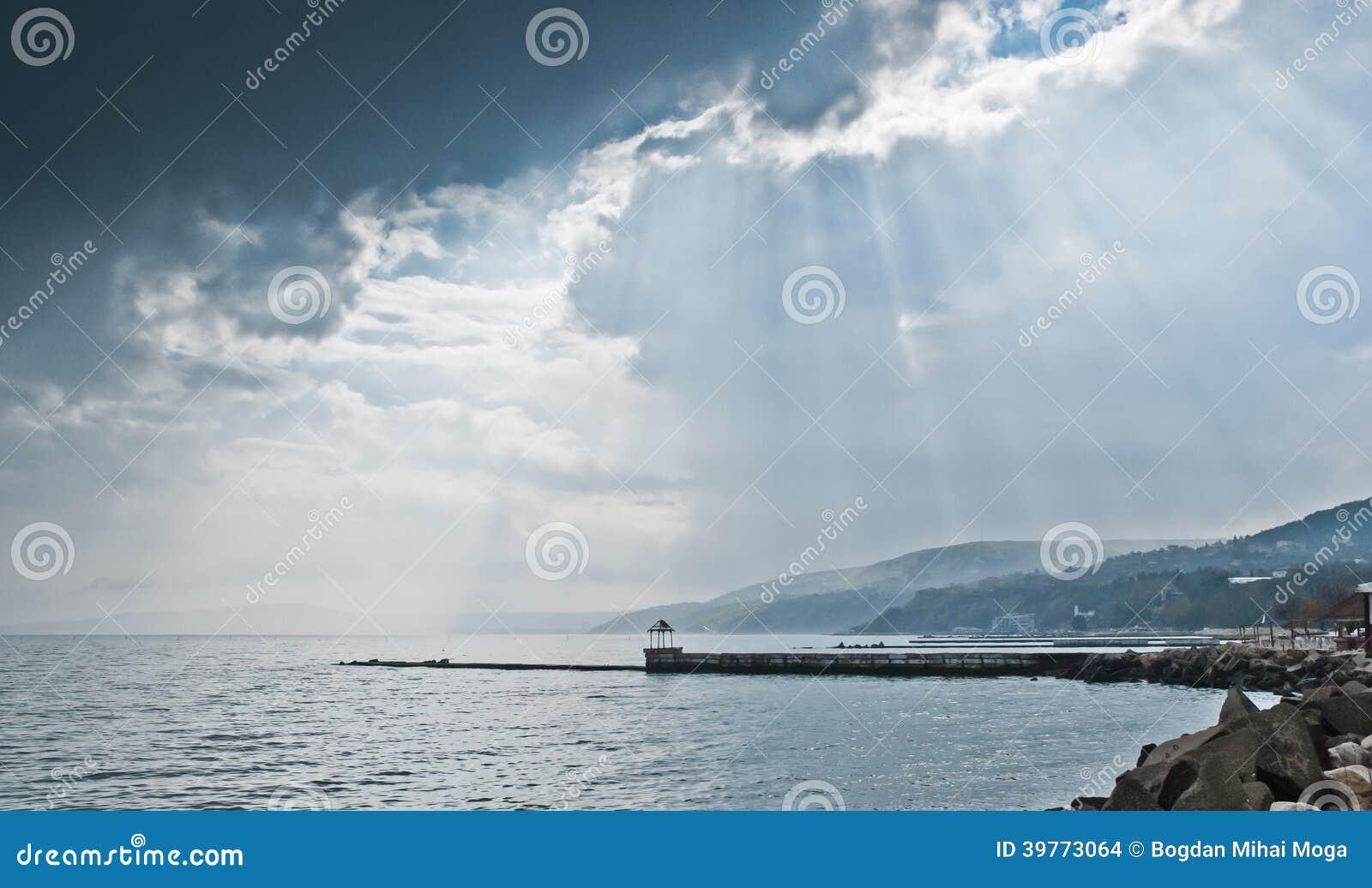 Strandboulevard met bergen en regenwolken