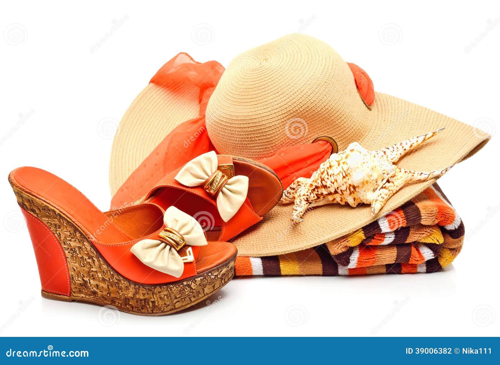 Strandhoed, handdoek, vrouwenschoenen en een zeeschelp