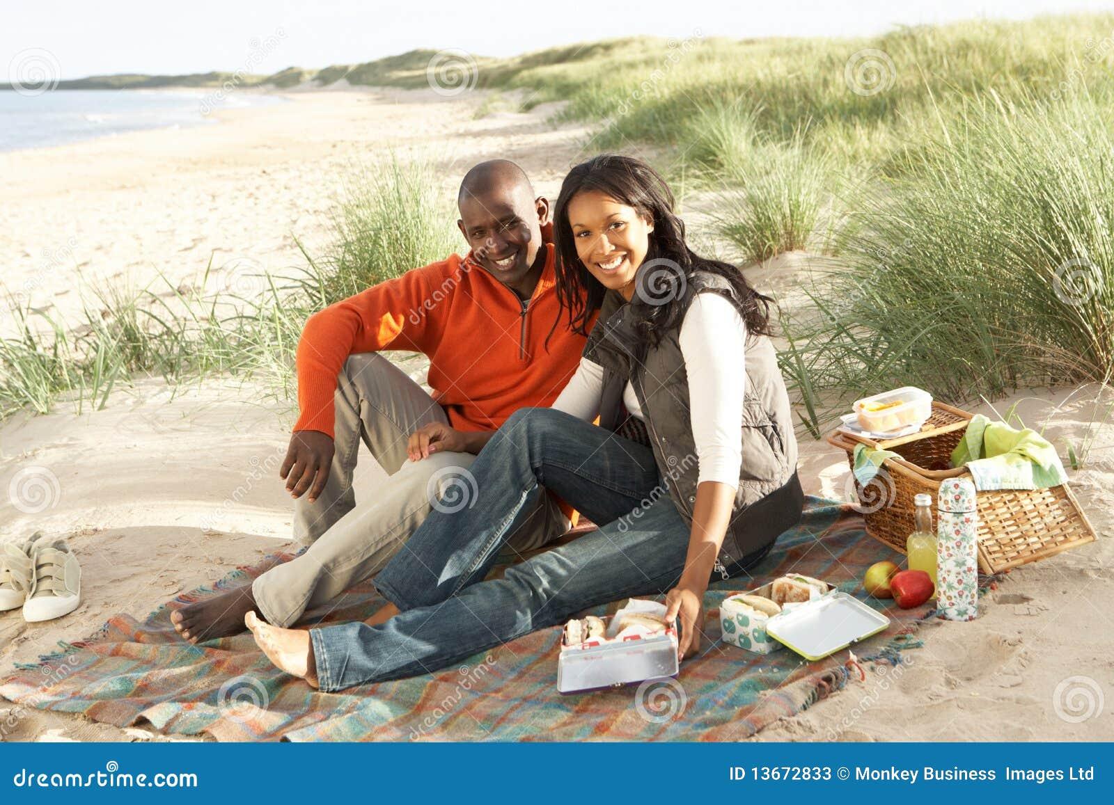 Strandpar som tillsammans tycker om picknicken