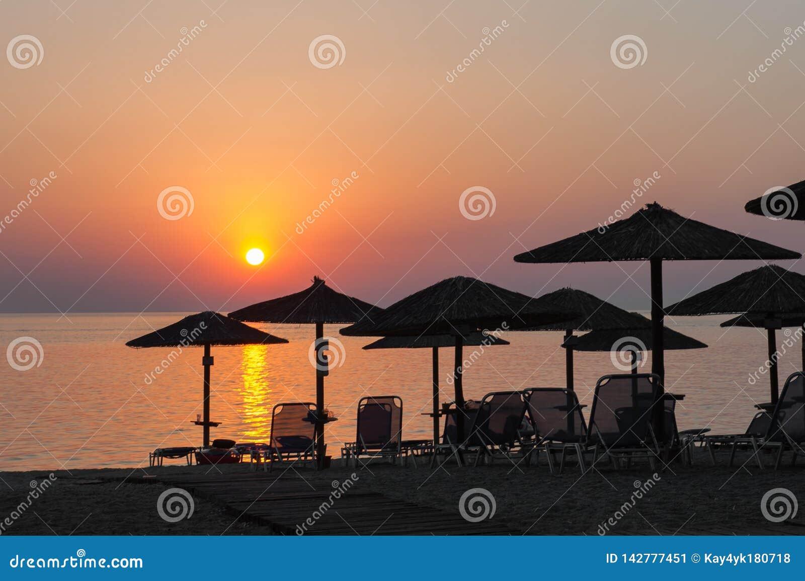Strandparaplu s bij zonsondergang, met sunbeds, hete zonsondergang op het strand