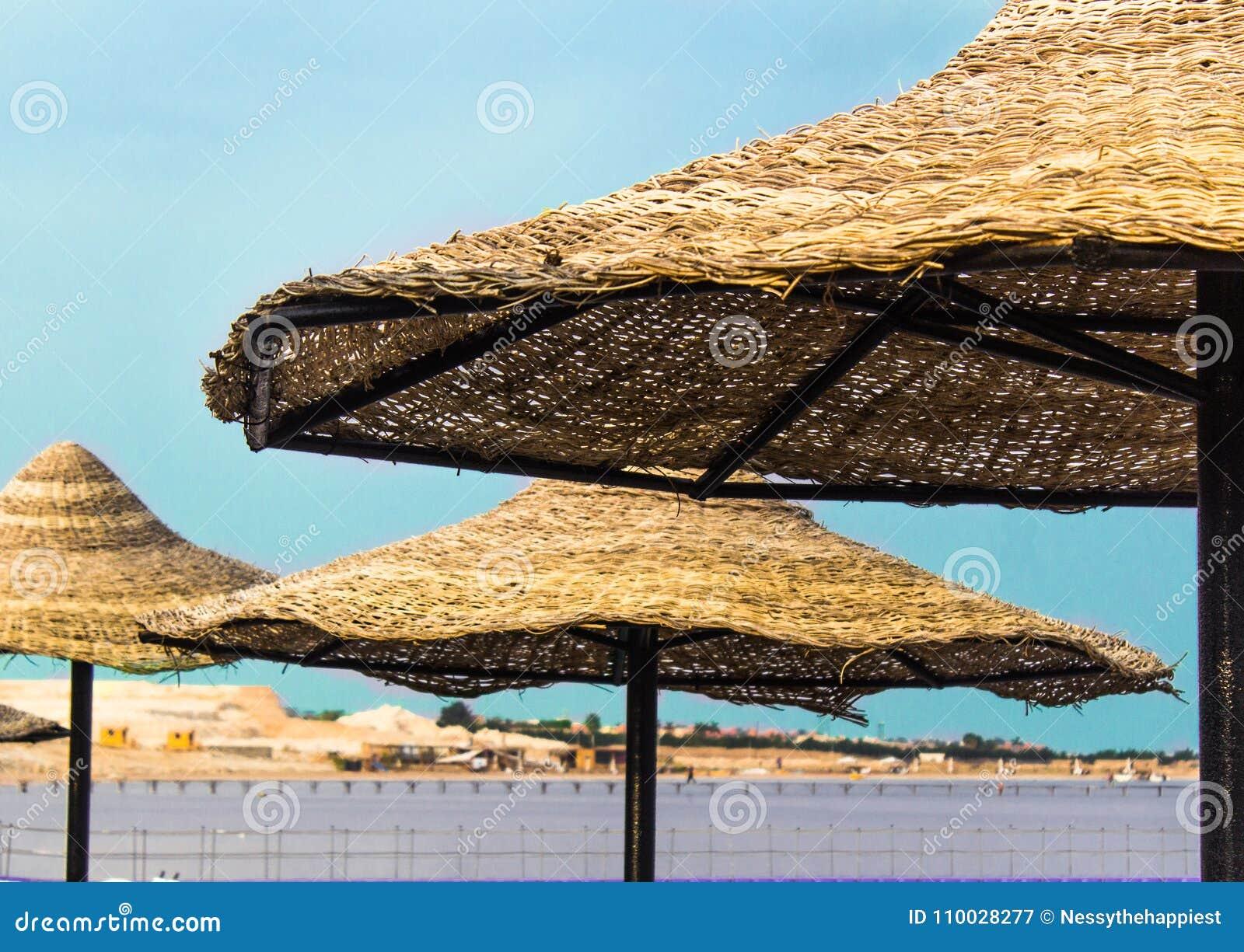 Strandparaplu uit stro drie het zeewater zandig strand van de sunshades blauw hemel op zonnige de zomerdag