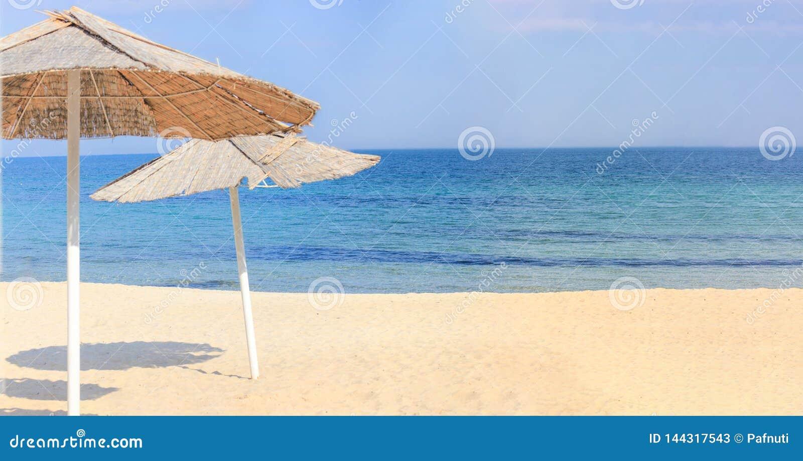 Strandparaplyer och ren sand mot