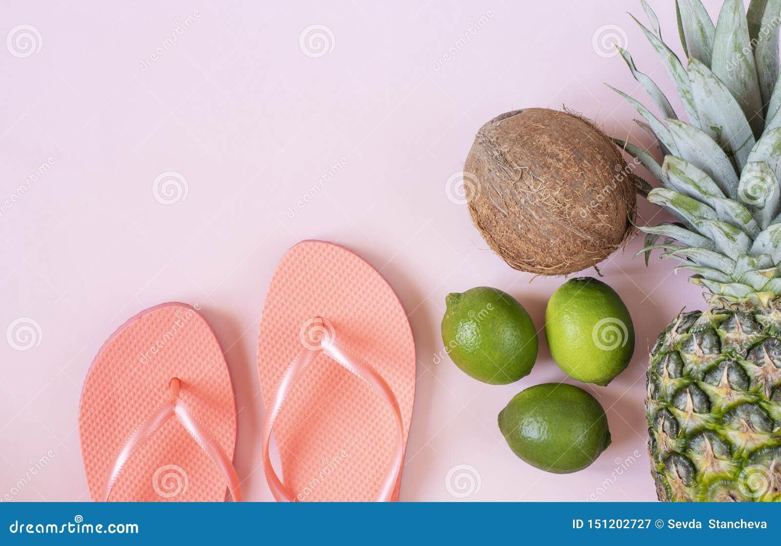 Strandtillbehör på rosa bakgrund - ananas, kokosnöt, limefrukt, badskor Sommar ?r det kommande begreppet