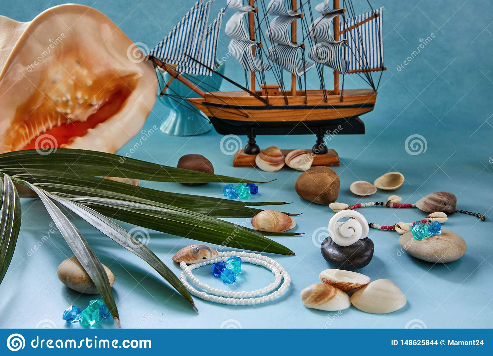 Strandtillbeh?r, sn?ckskal och fartyg p? en bl? bakgrund