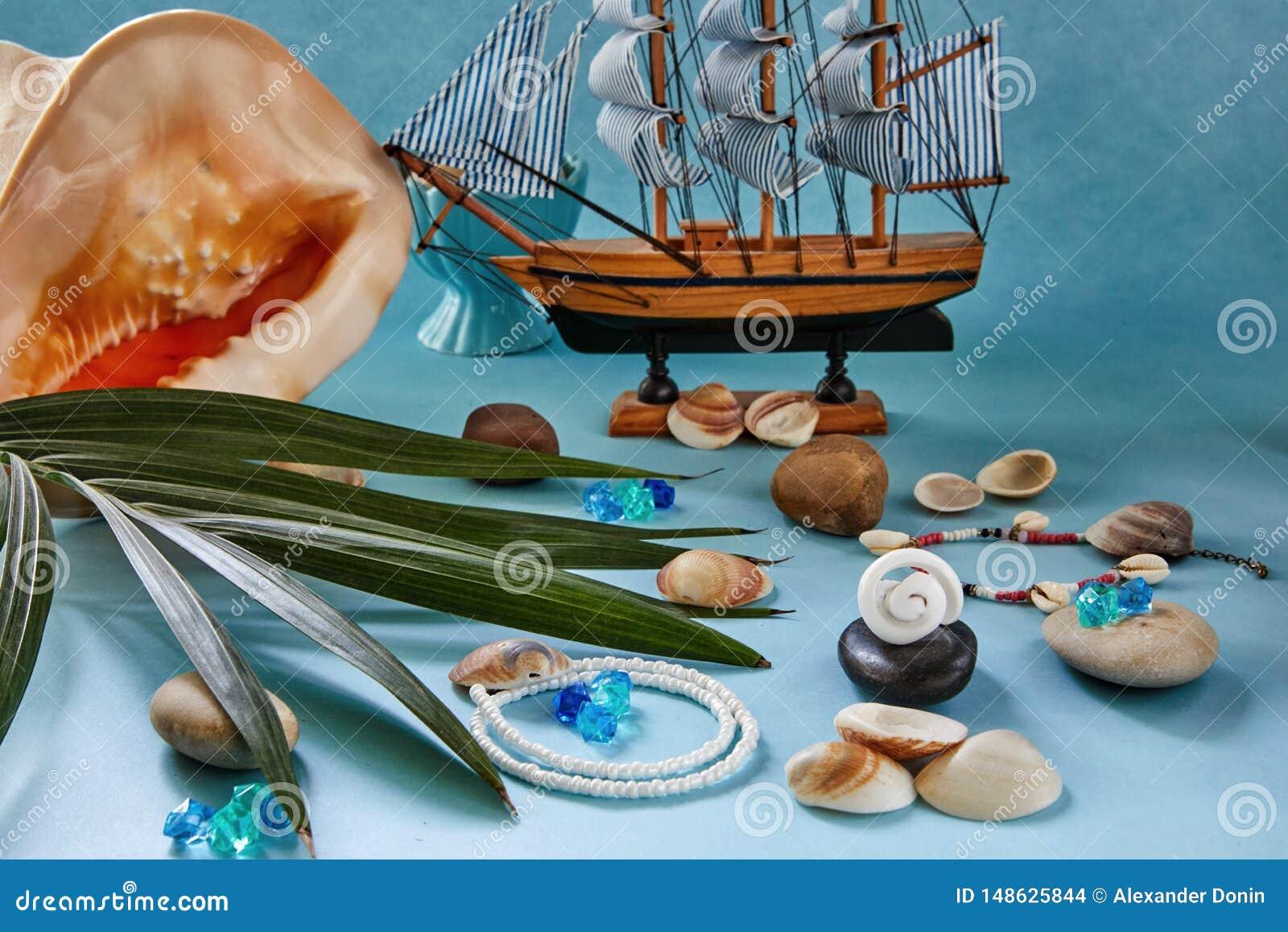 Strandtoebehoren, zeeschelpen en boot op een blauwe achtergrond