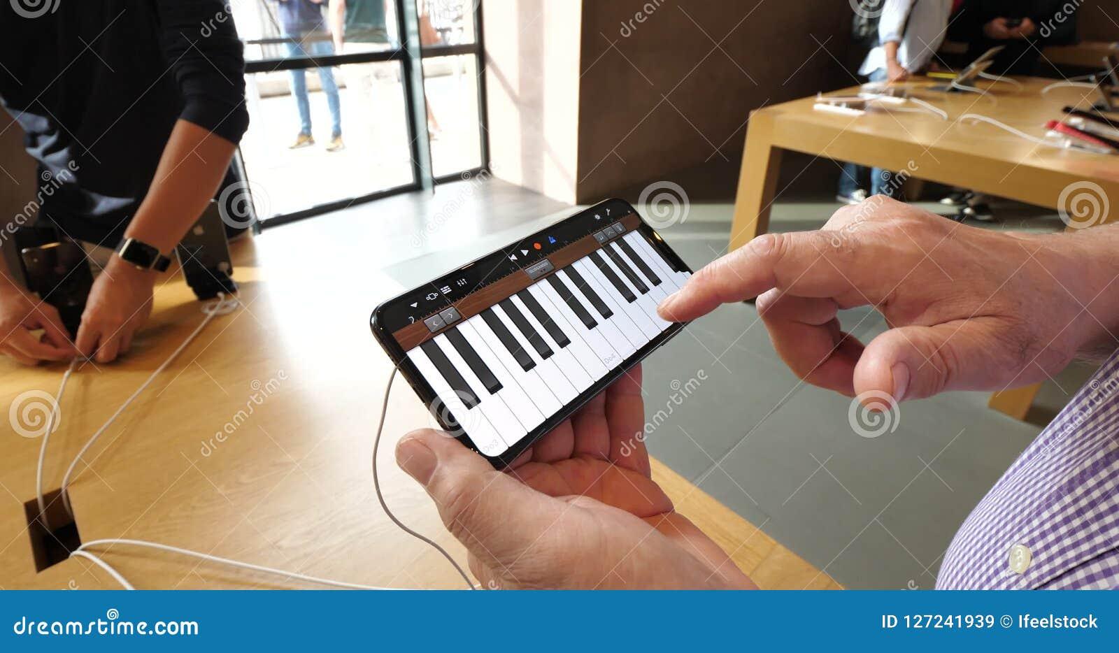 Piano Garage Band : Senior man playing piano on iphone xs max in garageband app stock