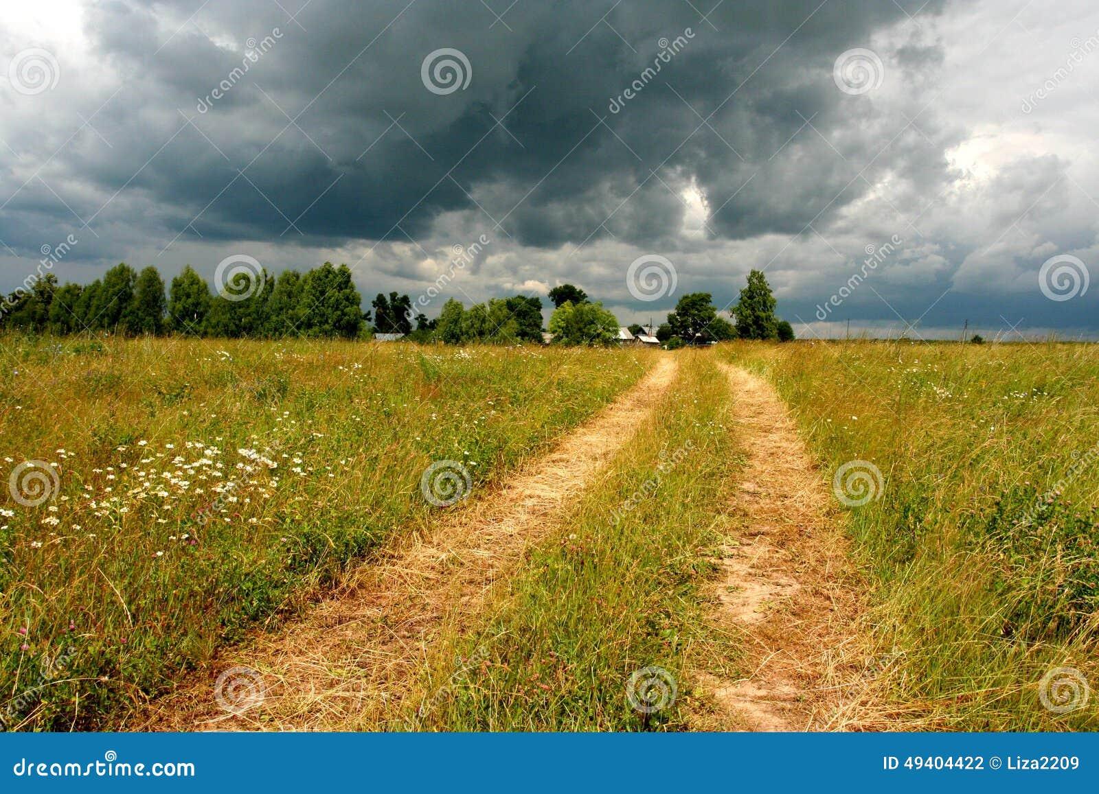 Download STRASSE Auf Dem GEBIET Mit DUNKLEN WOLKEN Im HINTERGRUND Stockfoto - Bild von dorf, himmel: 49404422
