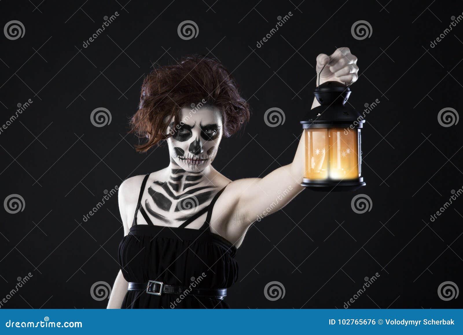 Straszna kobieta z lampionem nad czarnym tłem - Straszny wizerunek straszna kobieta z ciemnymi oczami i pojawieniem czarownica w