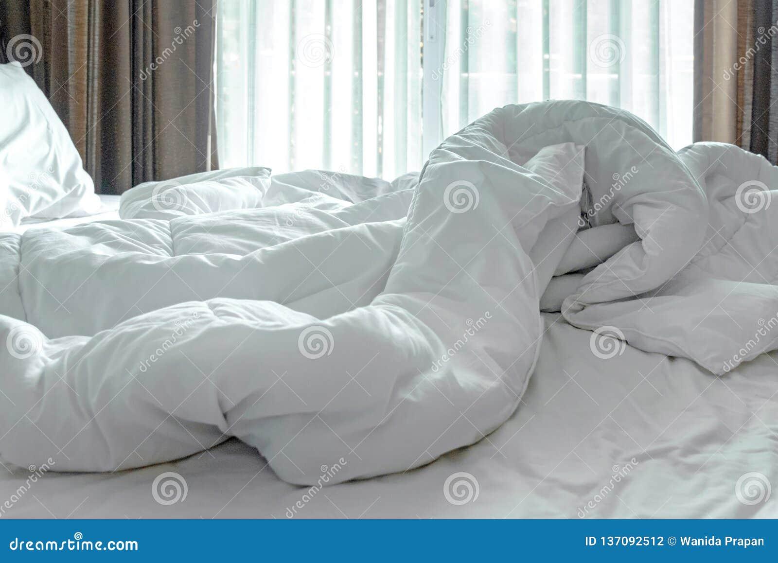 Strato, piumino bianco e cuscino del letto del materasso, incasinati di mattina nella stanza del letto