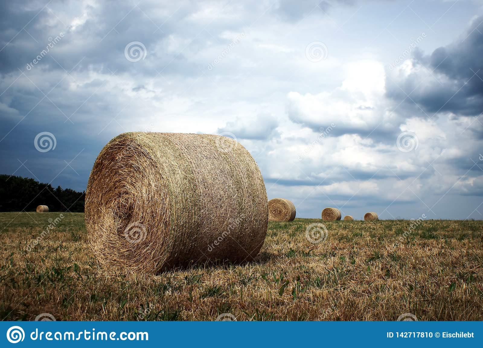 Straw bales under stormy clouds