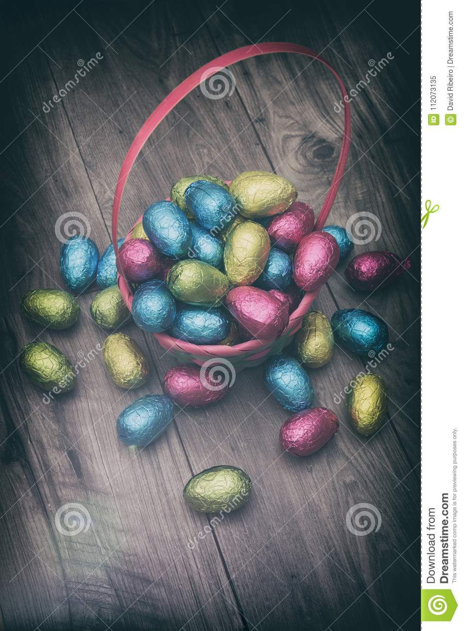 Straw basket filled with Easter chocolate eggs wrapped in colorful tinfoil