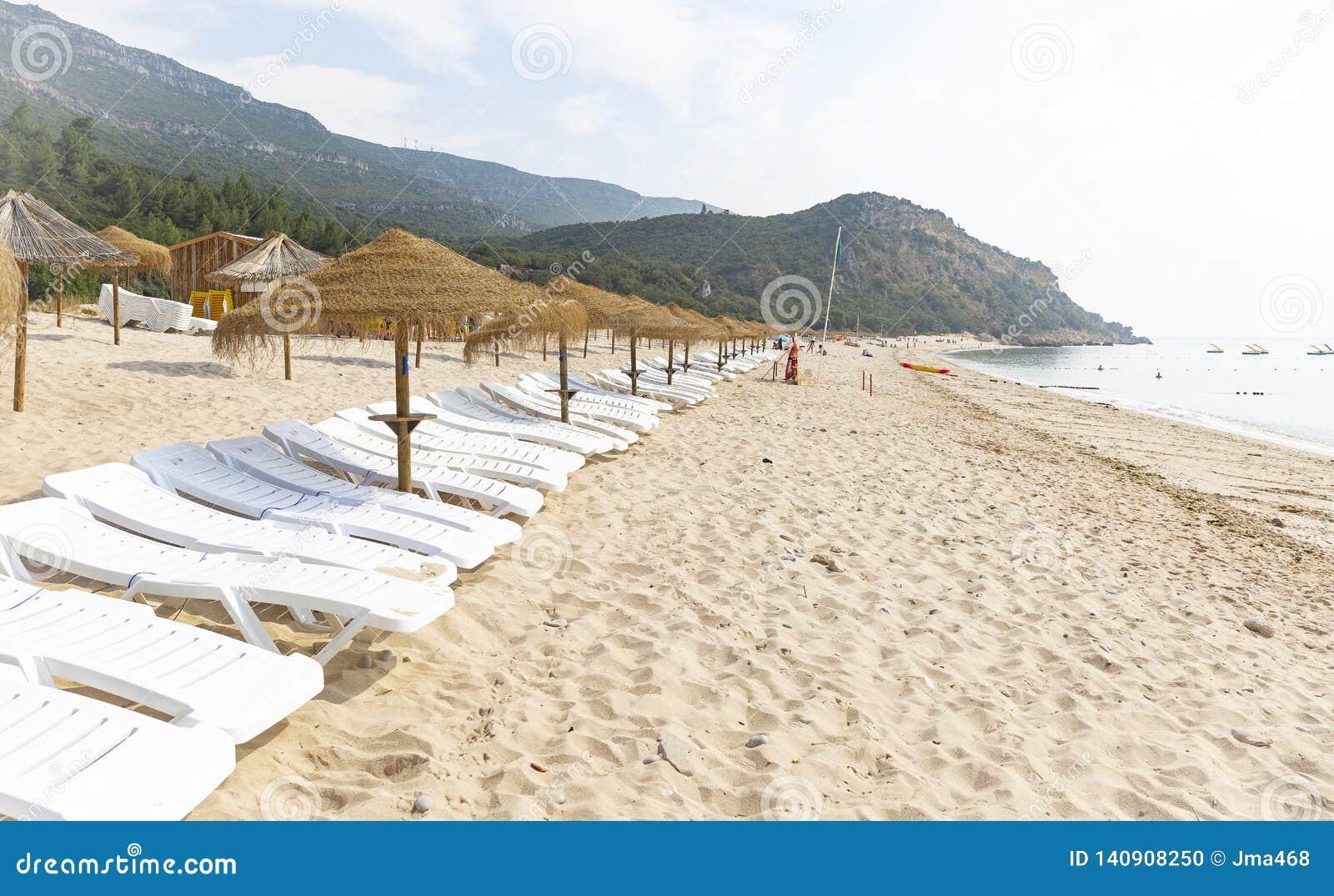Straw Beach Umbrellas och soldagdrivare på den Portinho da Arrabida stranden