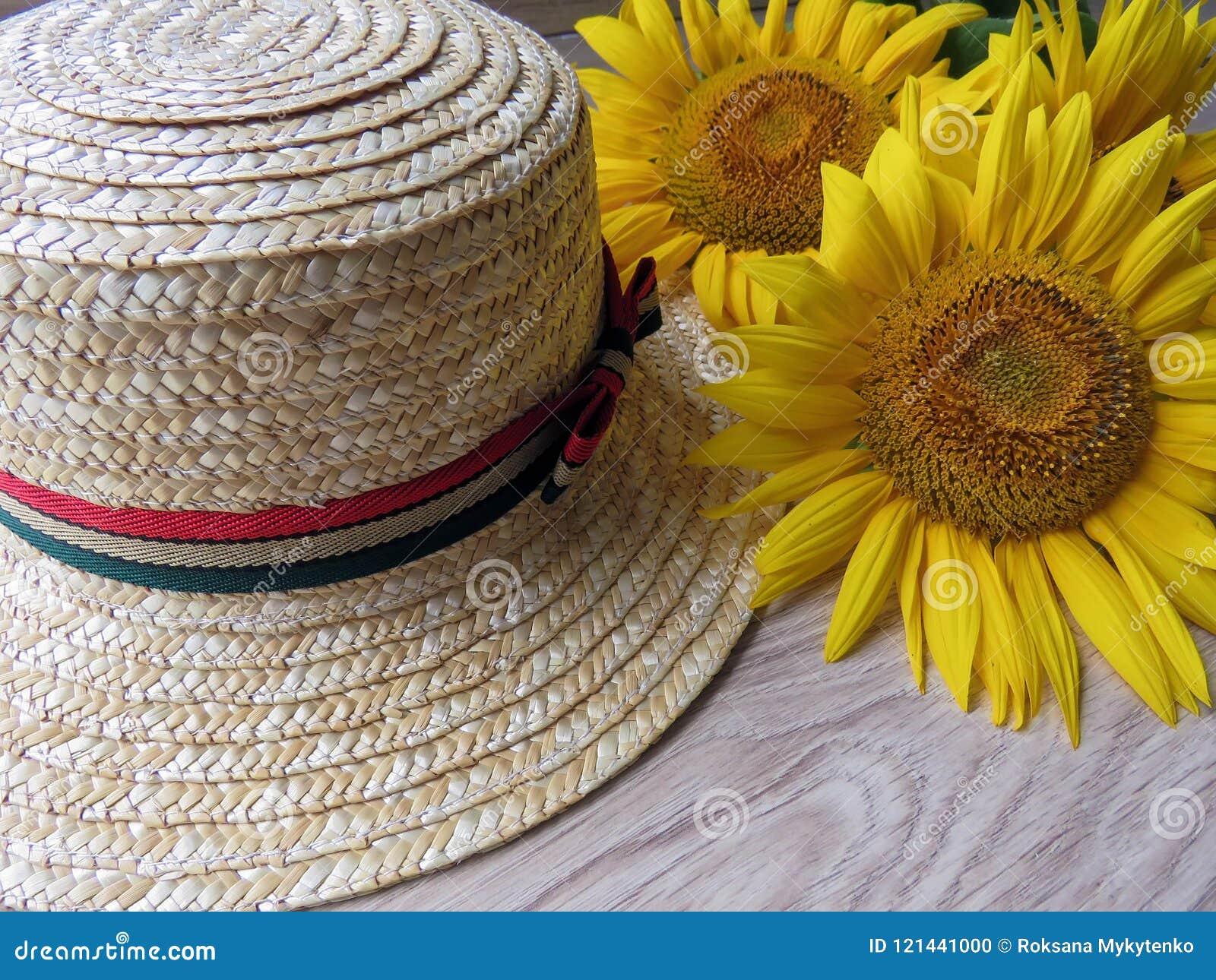 Straw Hat och solrosor på träbakgrund