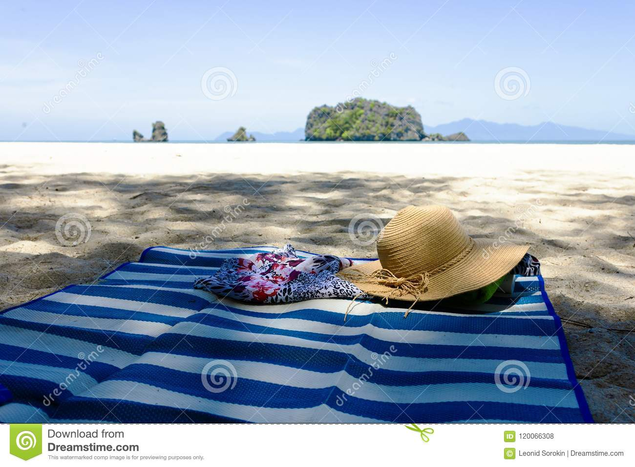 Straw hat, sunglasses and flip flops on a tropical beach.