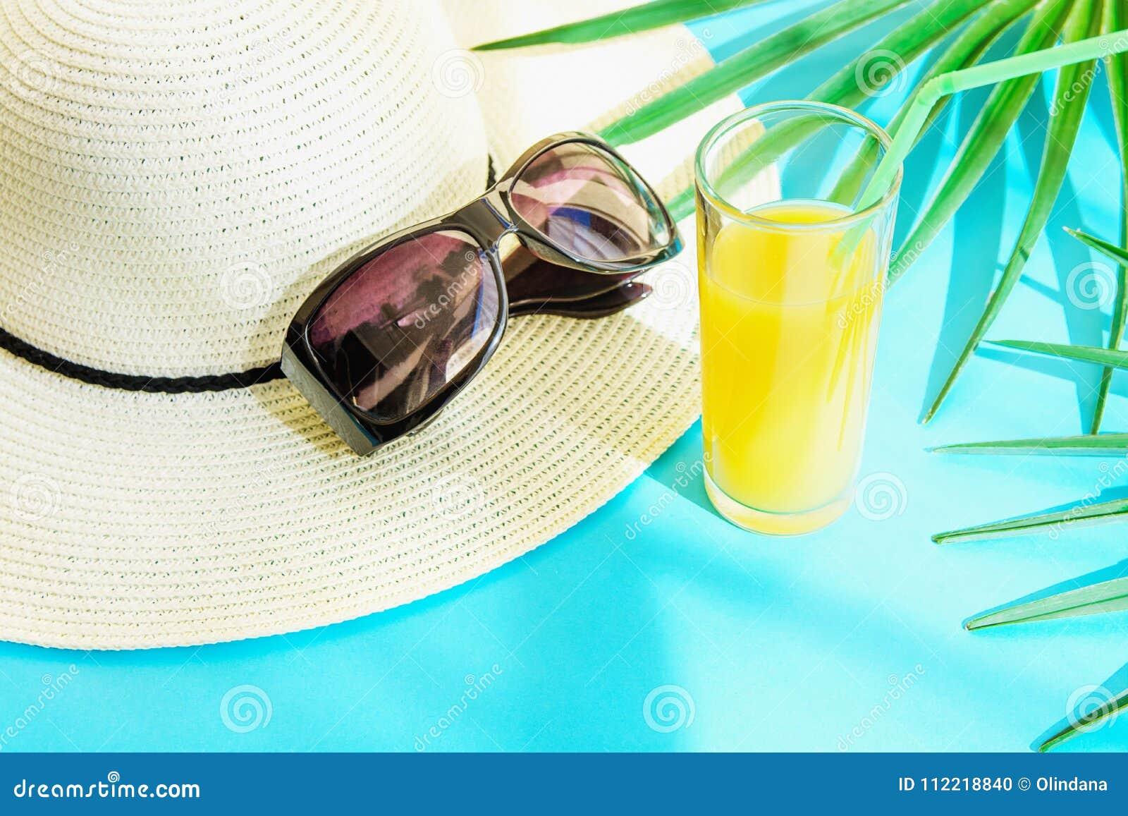 Straw Hat Sunglasses Tall Glass con la fruta tropical Juice Palm Leaves de la fruta cítrica fresca en fondo azul Escapes de la lu