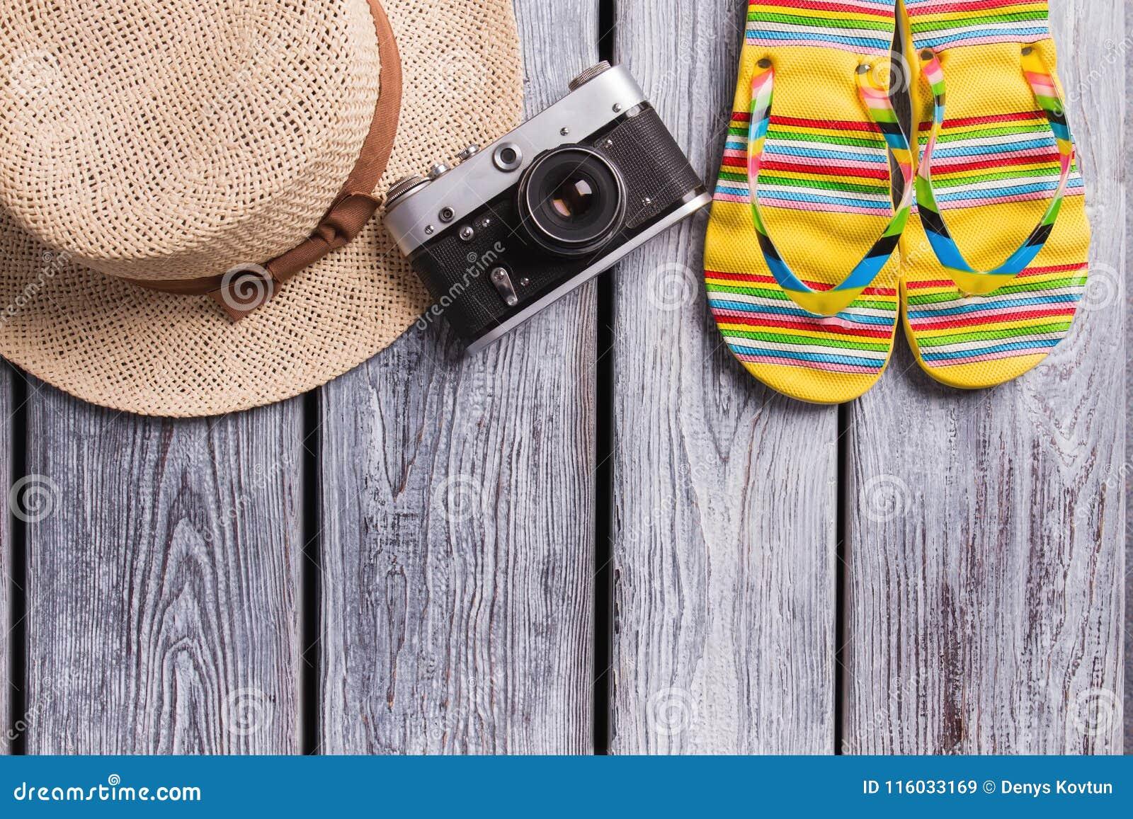 Straw hat, vintage photo camera and flip-flops.