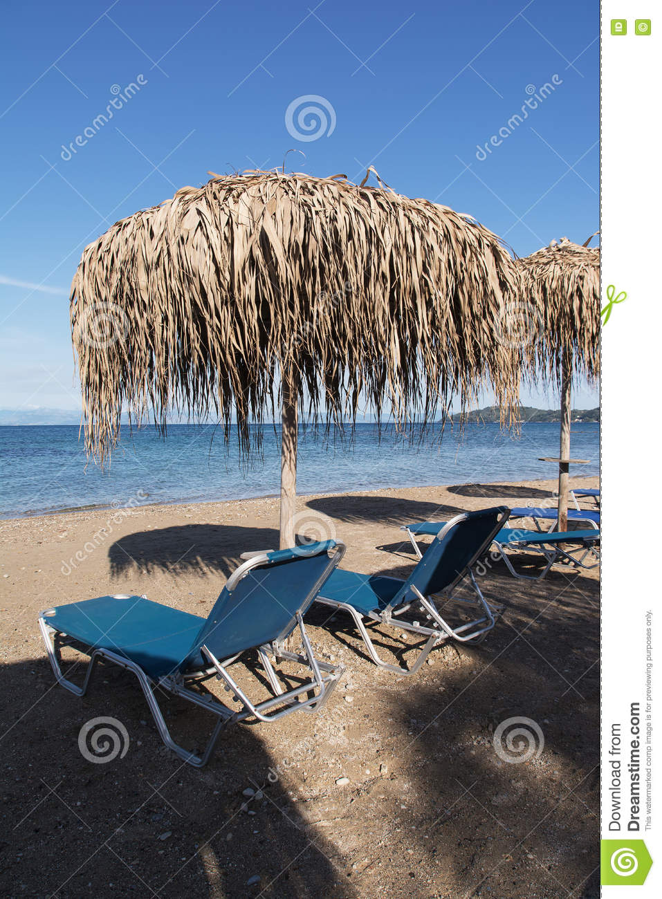 Straw umbrellas and sunbeds on a sandy beach, Corfu, Greece