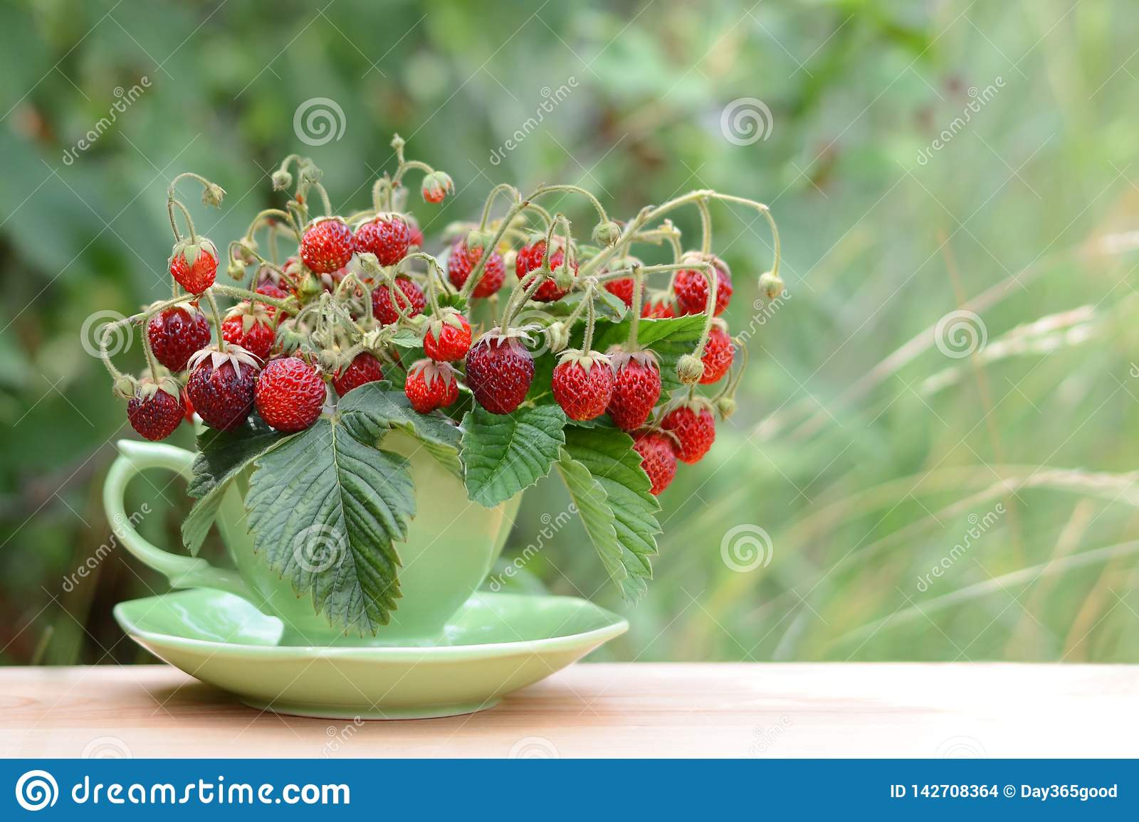 Strawberries in cup on green background. Summer natural background