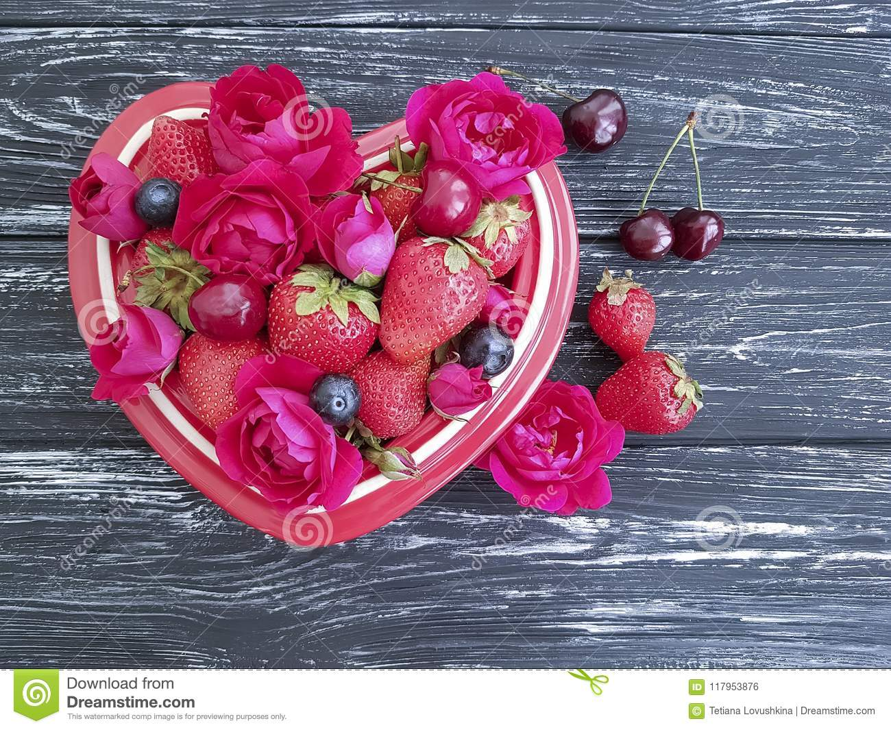 Strawberry, cherry, blueberry plate heart, vintage appetizing flower rose on a black wooden background