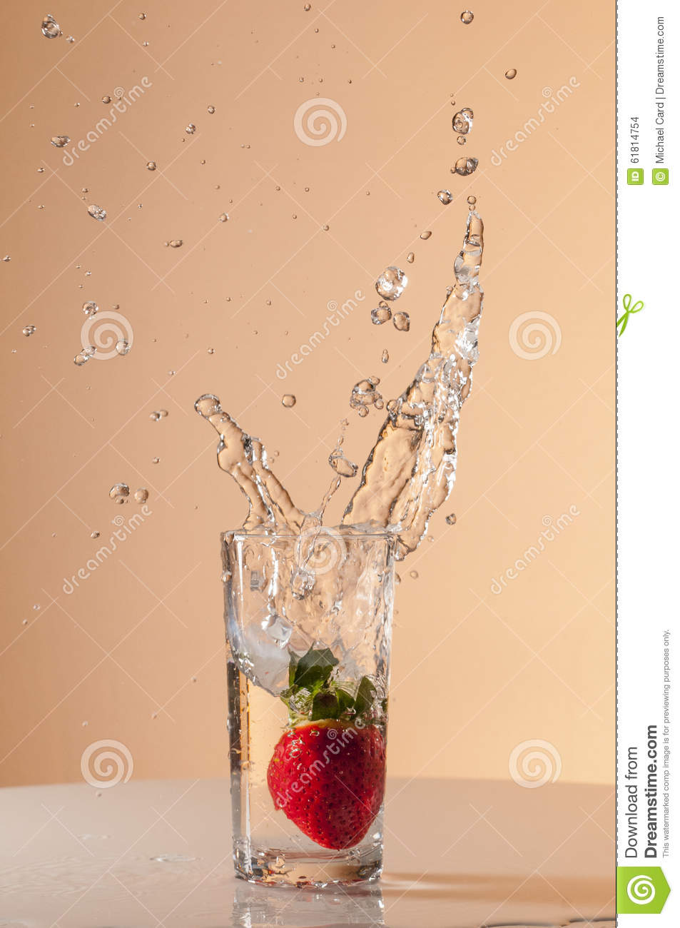 Strawberry dropped into glass of water