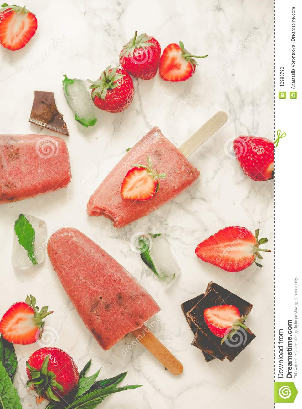 Strawberry ice cream with a banana and chocolate on a stick. Ton