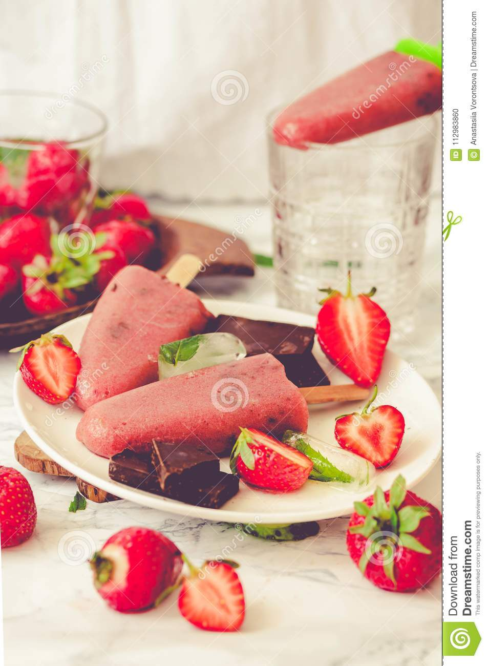 Strawberry ice cream with chocolate popsicles. Raw dessert. Mint