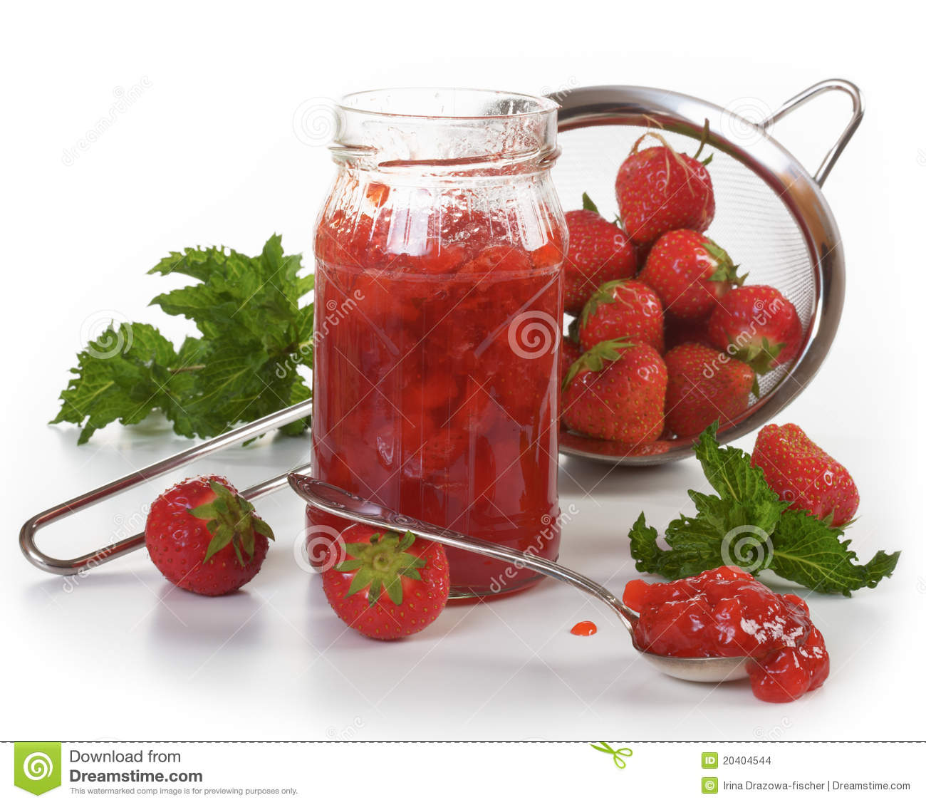 Jar of strawberry jam and fresh strawberries in a colander.