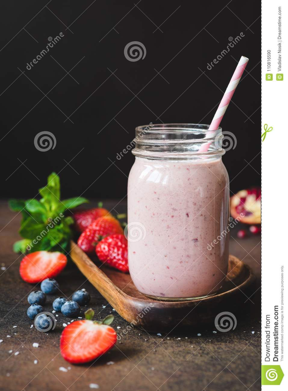 Strawberry smoothie in a jar with drinking straw