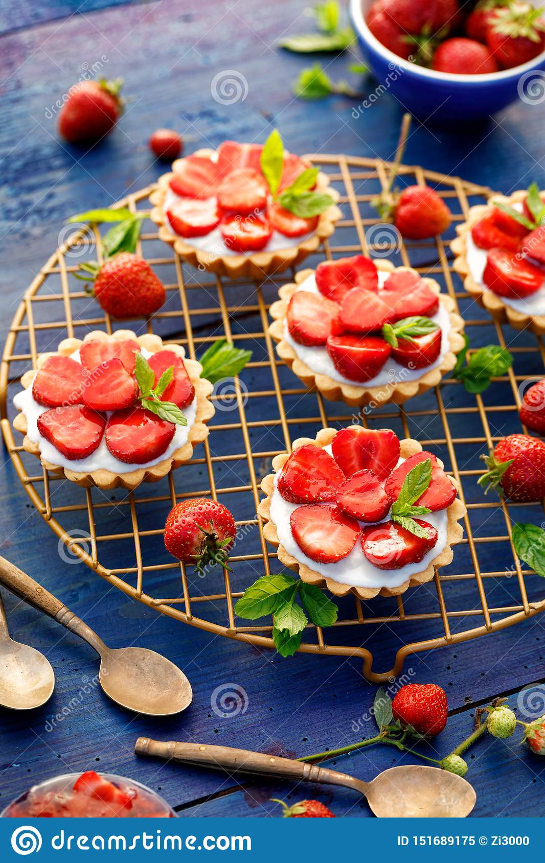Strawberry tarts, small shortbread tarts with the addition of cream cheese, fresh strawberries  on a cooling tray