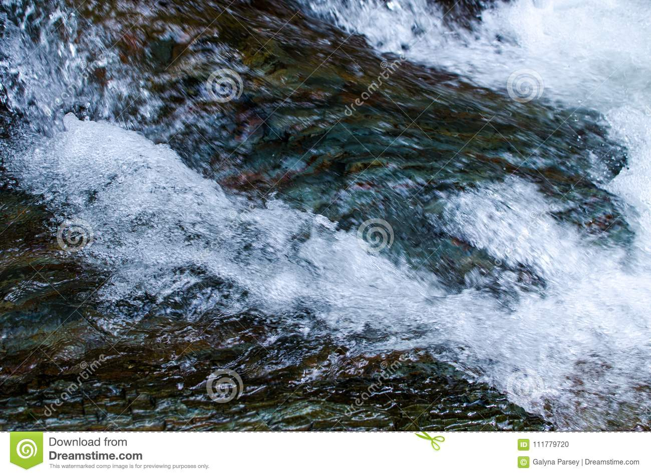 A stream in the mountains flows along the rocks and a stormy waterfall