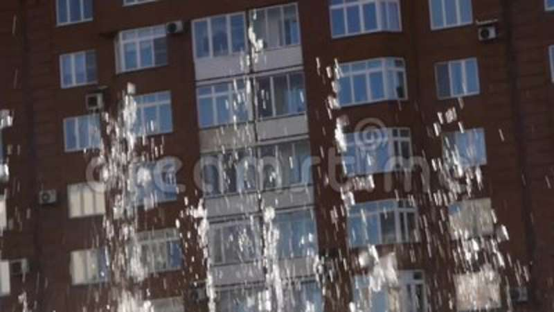 Streams of water of fountain on a city building background in sunny day. slow motion. Streams of water of fountain on a city building background in sunny day stock video