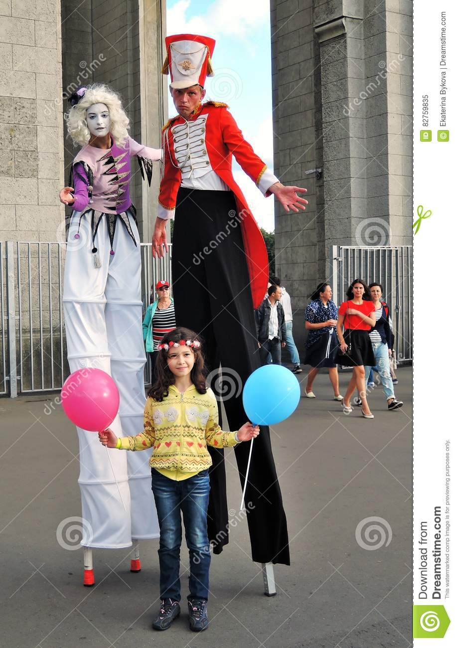 Street actors walk on stilts and pose for photos in Moscow