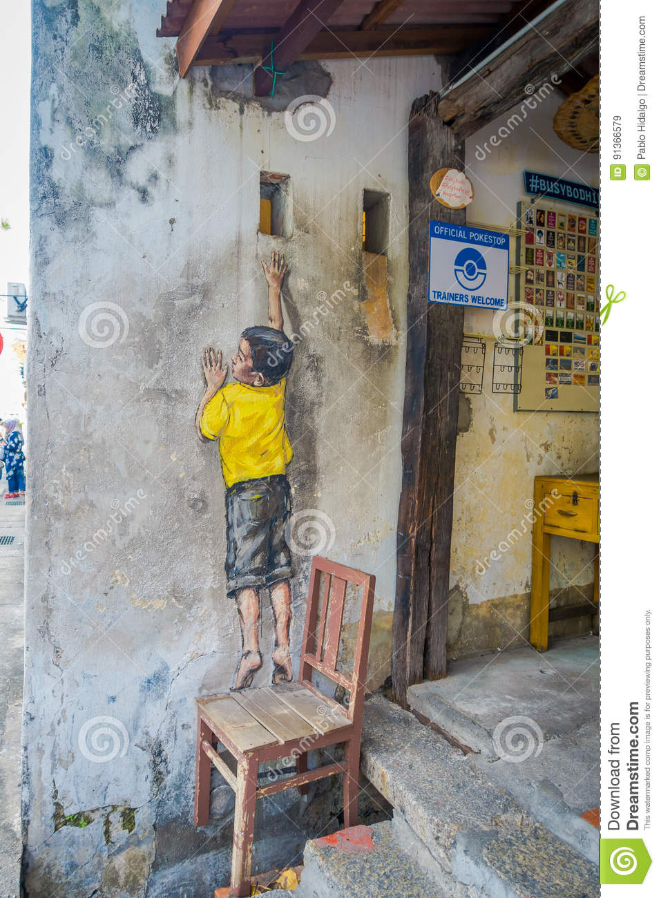 Street art graffiti of boy standing on a chair in george town city centre malaysia
