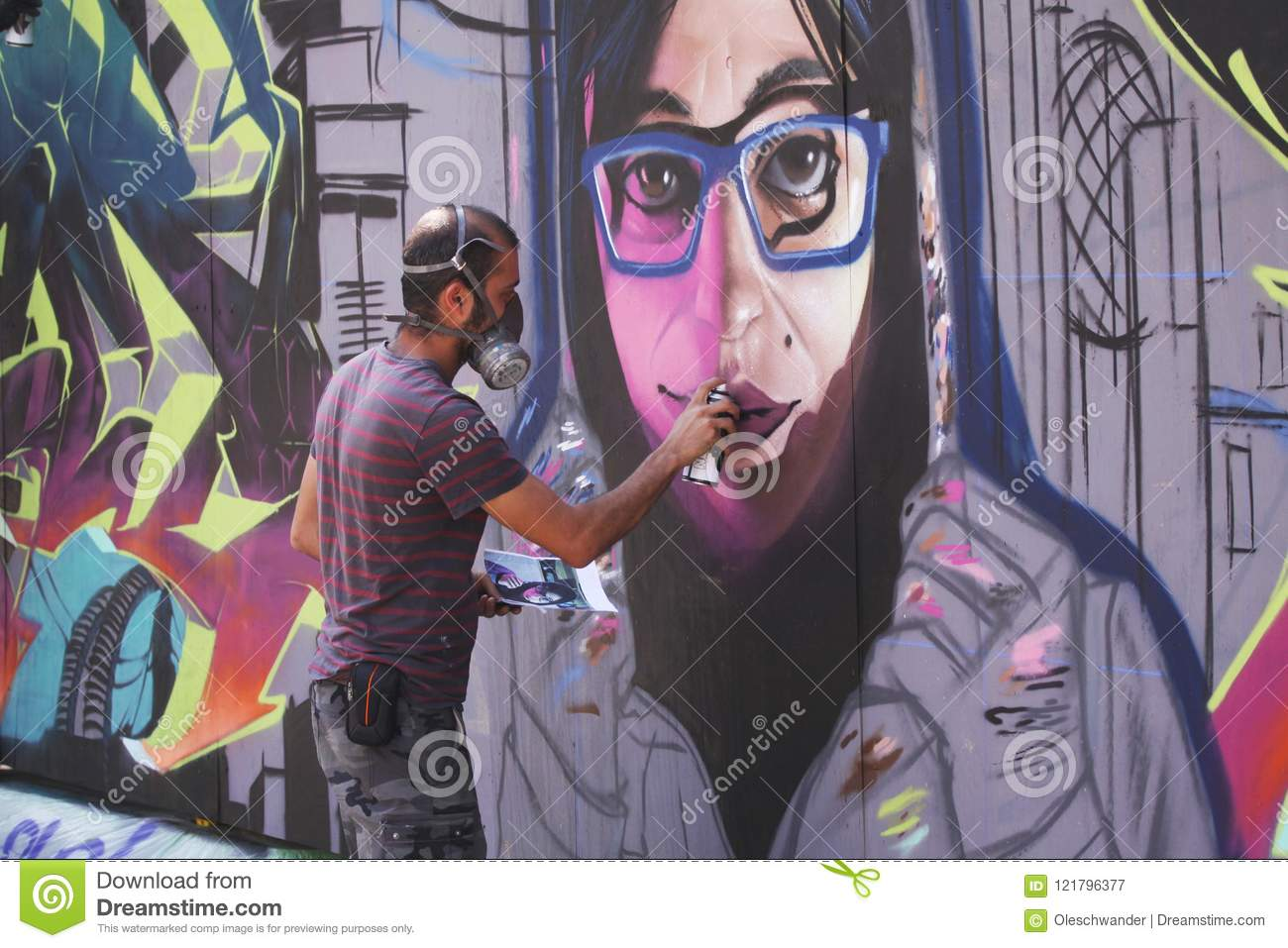 Copenhagen denmark july 20 2018 street artist painting colorful graffiti on wall modern art concept with urban guy painting live murales with aerosol