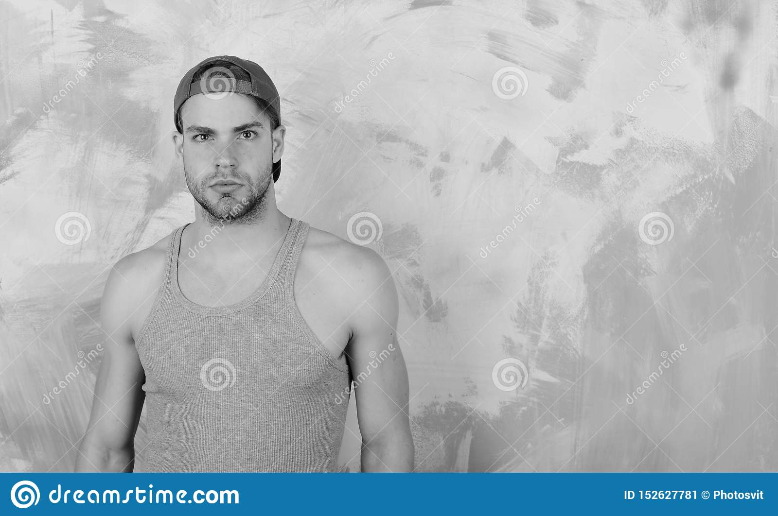 Street boy with interested face, copy space. Guy with bristle in grey tank top. Man in cyan green baseball hat on