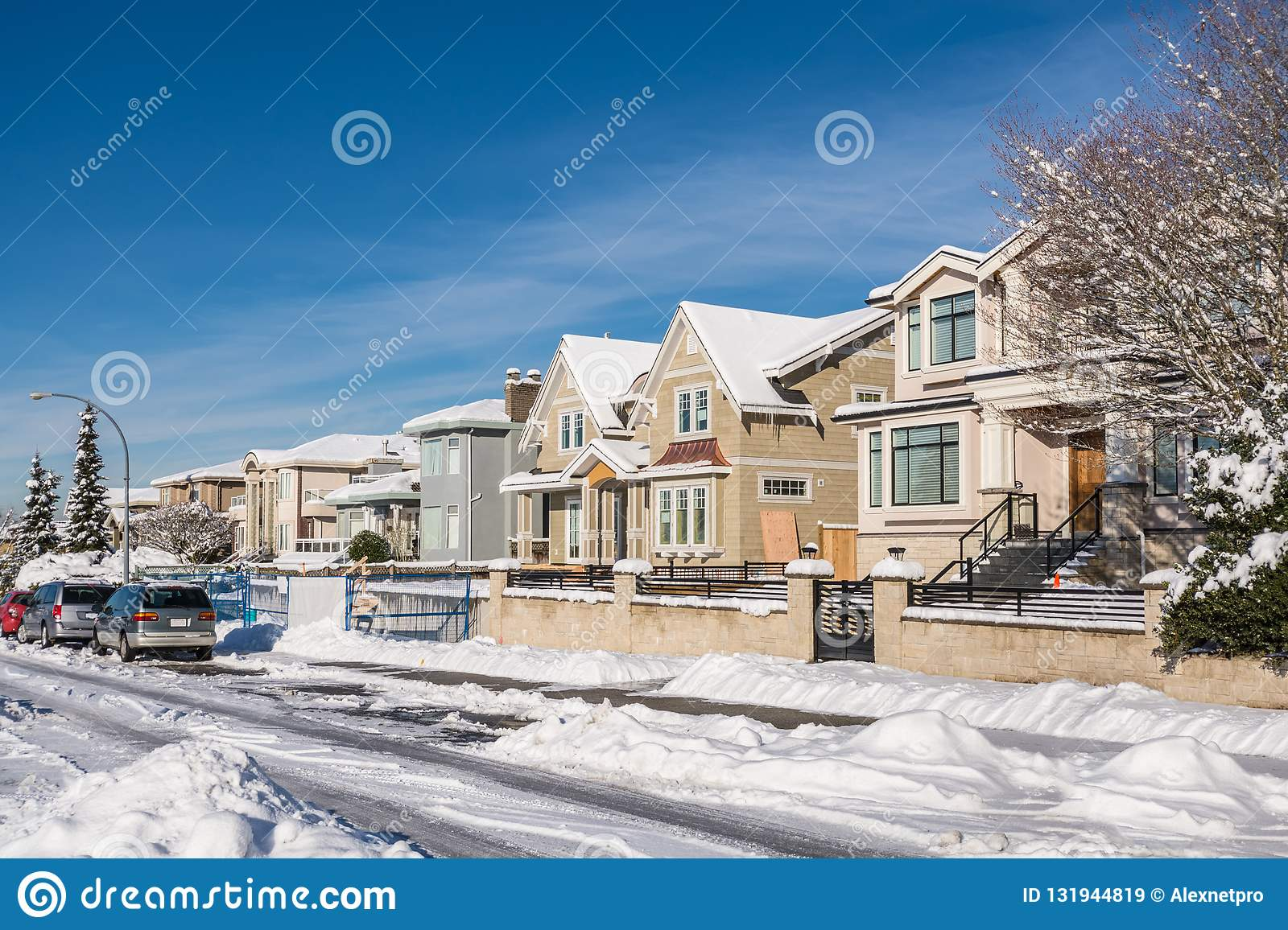 Street of brand new luxury houses on blue sky background in winter