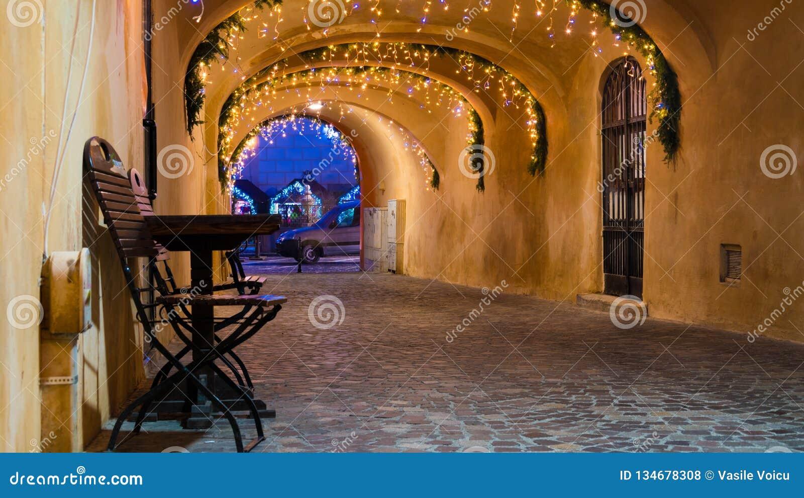 Street cafe at the night against city illumination lights