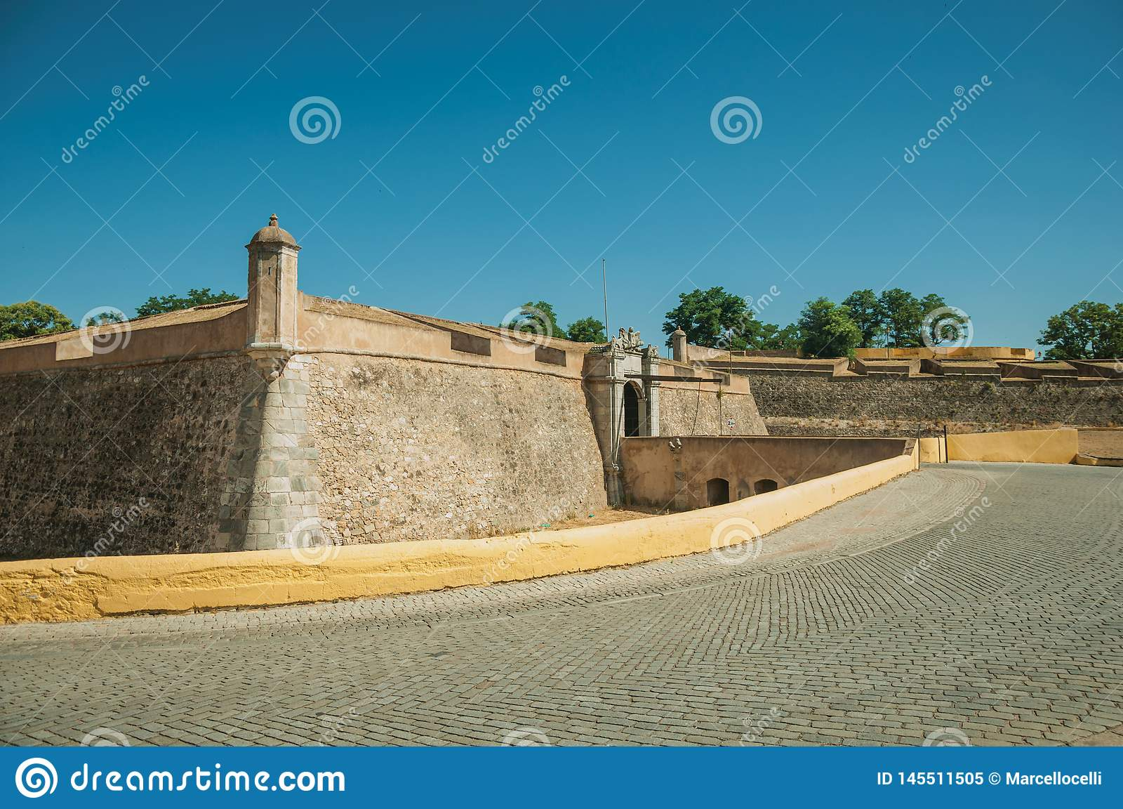 Street at the city wall with an entrance and small bridge